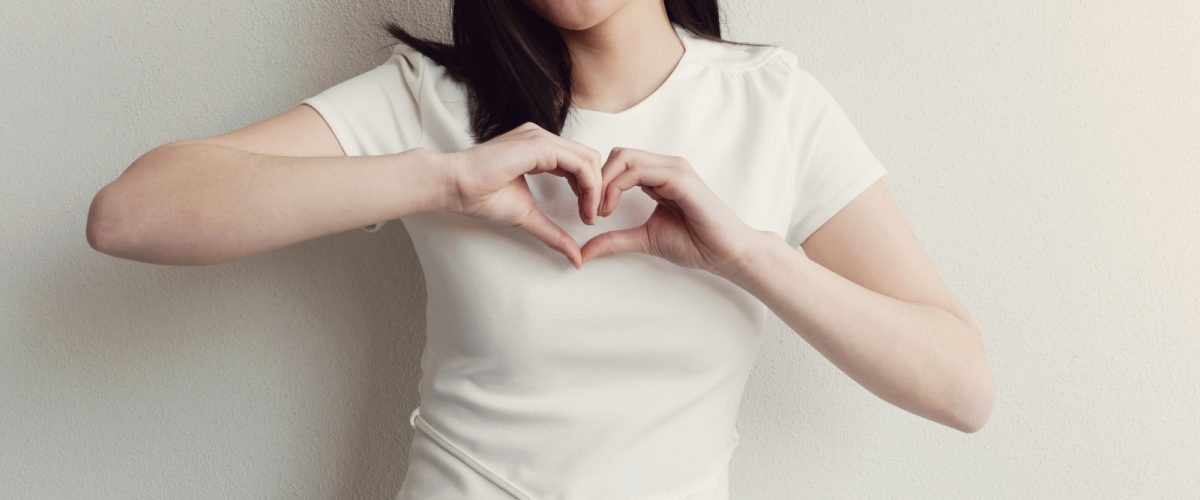 Happy Asian young woman making her hands in heart shape, heart health insurance, social responsibility, donation, happy charity volunteer concept, world heart day, International Day of Sign Languages